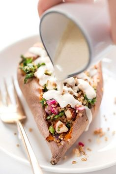 These AMAZING Quinoa Stuffed Sweet Potatoes are filled with kale, quinoa, hazelnuts and topped with a creamy tahini sauce!