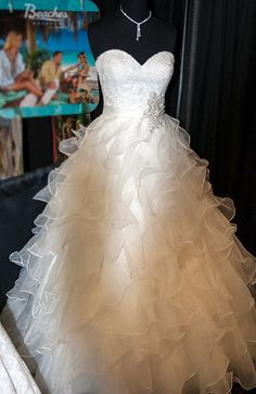 Beautiful ruffles in a full skirt ball gown style with sweetheart cut and a snowflake sparkle jewels  Lovely. Add straps and color!