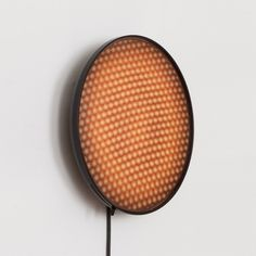 David Derksen's collection of wall lamps feature perforated discs that can be turned to reveal a shifting moiré effect