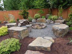rocaille jardin dans l'arrière-cour avec foyer extérieur en pierre et places assises en rochers