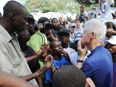 """Former US president and UN Special Envoy for Haiti Bill Clinton (R) listens to local residents on October 6, 2010 in a city camp in Port-au-Prince. The Clinton Foundation announced that it will, through its Haiti Relief Fund - provide 500,000 USD in bridge funding for a camp in Petionville run by the J/P Haitian Relief Organization. """"Rebuilding housing for more than 1 million people displaced by the earthquake will take time, as teams on the ground continue to clear rubble and build…"""