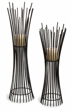 "Set of 2 Captivating Contemporary Pillar Candle Holders by CC Home Furnishings. $178.99. Set of 2 Candle HoldersItem #10657-2Tall wire form designMaterial(s): Wrought IronDimensions of each holder:Small: 27.5""H x 9"" DiameterLarge: 34""H x 10"" DiameterSet of 2 candle holders - includes one of each style shown"
