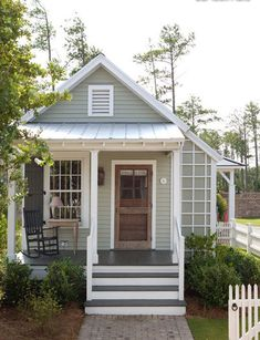 What a dreamy little cottage! Love that light gray/green color with the wood door