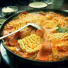 Budae Jjigae (Korean Style Stew) : Soon after the Korean War, when meat was scarce, Some people made use of surplus foods from US Army bases such as hot dogs and canned ham (such as Spam) and incorporated it into a traditional spicy soup. This budae jjigae is still popular in South Korea, and the dish often incorporates more modern ingredients such as instant ramen noodles.