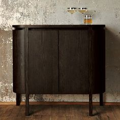 Solid ash legs and engineered wood frame.     Smoke-stained ash veneer.     Two adjustable center shelves.     Two side cabinets for bottle storage.