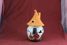 """Create a nice atmosphere in your home with the fragrance from this fairy-tale like diffuser. Add sensual oils of your preference on the saucer provided and see the smoke drifting from the chimney when lighting the t-candle inside the """"Fairy House"""".  This object is made of low-temperature clay, the technique Sgraffito and many different dots colors.  Weight= 800 gram Height= 23cm"""