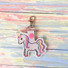 Featured is a beautiful glitter unicorn keychain stitched out on vinyl. She is magical and ready to bring her pizazz to your key ring. Fun uses… - Perfect for people who love unicorns or believe in magic - Backpack Tags - Stocking Stuffers - Luggage Tag - Classmates Gifts - Clip it on your purse - Attach to a lunch box - Memorable Party Favors - Birthday Gifts - Not just for keys. Attach it to your children's items to help them distinguish their stuff  For orders, larger than 5 keychains…