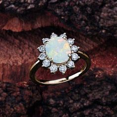 This opal halo engagement ring in 14K white gold features an oval opal center stone that is complemented by brilliant white, sparkly diamond side stones. Opal Engagement Ring Details: 100% Handmade in the USA Center Stone - Opal (1.10 carat AAA) Metal - 100% Solid 14K (In Rose, Yellow, or