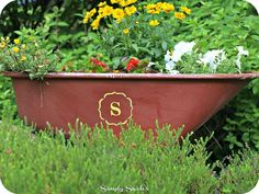 Hometalk :: DIY Wheelbarrow Planter Would love to do this with the old claw foot bathtub. Paint last name in stencils... paint exterior of tub rust/deep red. Stencil in yellow like on this one.