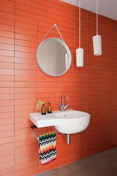 A wall of rustic, brick-orange terracotta tiles provides a warm backdrop to the grouping of mirror, basin and pendants in the powder room.
