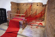 In 2011, Brazilian artist Tatiana Blasspierced the walls of a Sao Paulo chapel with large masses of red yarn, letting the bright material trail into the surrounding grasses, landscape, and trees. The installation, titled Penelope, was named afterOdysseus's wife inHomer's Odyssey, a