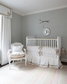 Chic girl's nursery design with gray walls framing white Jenny Lind Crib