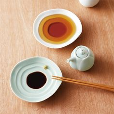 A soy sauce dispenser and saucer in the shape of a lotus or haas flower. Saucer has topographic measuring rings. By Miyama, Japan