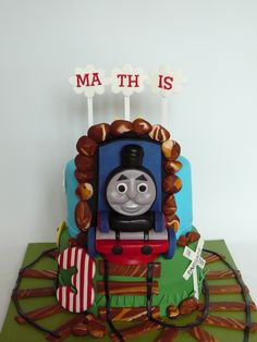 Thomas the train - My version of Thomas the train cake. Chocolate cake with buttercream covered with fondant. All details are fondant, everything is edible except for the sticks on the clouds and the sun.