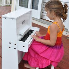Whether indoors or outside, Ella enjoys playing her conveniently portable upright spinet.