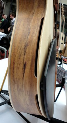 The soundholes are located at the sides and to strengthen to body to keep the tension with a thin top there are two bottoms. One hidden maple.