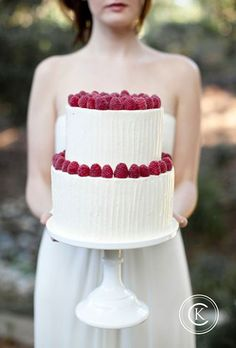 Brides.com: . A two-tiered textured white cake, topped with ripe raspberries by Sweet and Saucy Shop.