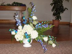 Arrangement with blue orchids, white hydrangea, roses and filler.