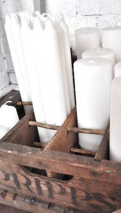 White candles stored in old wooden box.