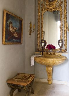 In the powder room of a Houston home, a Louis XV mirror is set above a Siena marble sink with 1940s bronze fittings.