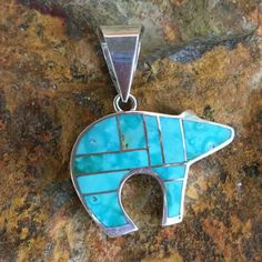 """This beautiful Sterling Silver Bear Pendant features Watermark Kingman Turquoise. It is reversible with a sterling silver finish. Dimensions: 1 1/8""""W x 3/4"""" (not including bale) The Pendant is designe"""