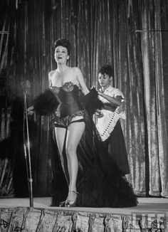Gypsy Rose Lee (L, Fore), receiving help out of her clothes by her maid, during act in Royal American Show. Location:Memphis, TN, US Date taken:1954 Photographer:George Skadding