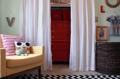 i love the idea of curtains instead of doors on a closet in a (small) kids room.  i think it opens the room up, adds more opportunities for design- like the pop and color of the red dresser, bins, and shelf-organizers-and gives kids visual incentive and more physical control over dressing themselves, which is a great thing when they are ready for it!
