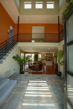 This modern tower entryway features high windows for abundant light, slate floor tiles, black steel stairway railing, and an orange accent wall.