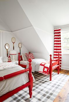 Look closely! These beds aren't an exact match. Coated a glossy red, they have a cohesive look with just the right dose of country.  And the fastest way to make a room feel even more homey? By placing a large rug underfoot. Here, a plaid Dash & Albert design creates a visual anchor to ground the fiery beds.   - CountryLiving.com