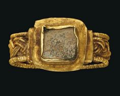A LATE ROMAN GOLD AND GLASS RING   CIRCA 4TH CENTURY A.D.   The hoop composed of two bands of triple wires woven together with beaded wire edge, the square bezel with green glass inlay  5/8 in. (1.5 cm.) wide