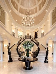 Grand Black and White Entryway With Double Staircase