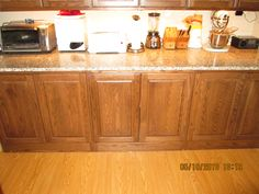 "Six Craigslist kitchen cabinets and a 34 inch deep by 118 inch long Craigslist granite countertop installed in my kitchenette. There is a 12"" wide by 24"" tall cement ledge underneath the back foot of the countertop. The countertop rests on a 2""x4"" ledger board, screwed into the back wall, and sits on the 34.5"" tall by 18"" deep base cabinets. There is no recessed toe kick. These were all built to be pantry cabinets, but got returned and listed on Craigslist."
