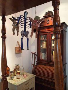 Bedroom in Frida Kahlo's home, angels dangling, medicine still on the table.