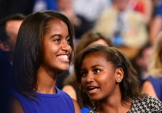 First daughters Malia (L) and Sasha (C) confer as US President Barack Obama delivers his acceptance to run for a second term as president at the Time Warner Cable Arena in Charlotte, North Carolina, on September 6, 2012 on the final day of the Democratic National Convention