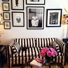 Sensational striped sofa. Amazing wall of framed photos. Striking room. {at the office : a glimpse inside the elegant world of carolina herrera}