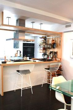 Love the pot rack and cookbook storage. I like the idea of using that kind of bookshelf in the kitchen; it would hold just the right amount of cookbooks. The barstools are cool too.