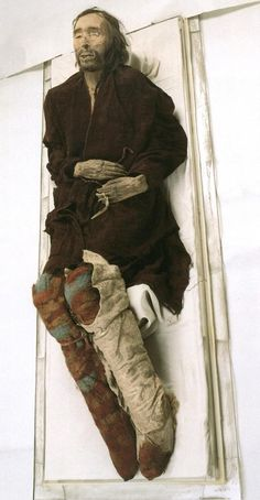 """Cherchen Man Mummy c 1000 BC China is 6 feet tall, wears a red twill tunic & tartan leggings. He was around fifty years old at death, has reddish brown hair, a long nose, full lips & a ginger beard. He was buried with no less than ten hats, one looks Roman, another looking like a beret, a cap, & even a conical """"witch"""" hat. He has a yellow tattoo of a rayed sun on his left temple. These Caucasion peoples are thot to be of Scottish origin due to Tartan weaving style and wool"""