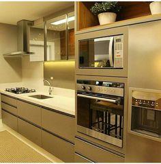 Simples e glamuroso! A cor dos materiais usados - um ouro velho - e o charme e praticidade que é o forno embutido e os acendedores ao lado da pia. Perfeita!