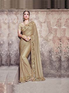 ​An exclusive saree for royal look. Golden imported fancy fabric saree with gota blouse
