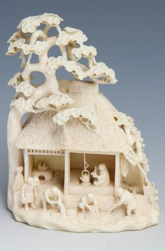 """Description: JAPANESE CARVED IVORY OKIMONO TEA CEREMONY Japanese carved ivory okimono depicting a genre village scene and tea ceremony. Intricately carved details to thatched roof and evergreen tree. Signed on underside. Weight: 80.2g Size: 3.25"""""""