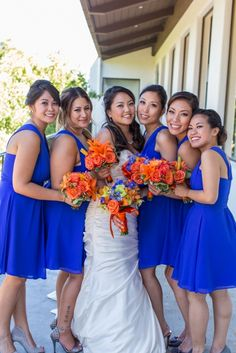 Brightly colored bridal bouquets of orange flowers pop off the girl's cobalt blue bridesmaid dresses. Orange bridesmaid bouquet by Seasonal Celebrations. Photo courtesy of Our Digital Studio.