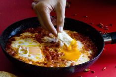 Receta de huevos en el purgatorio. Plato festivo de origen florentino con un intenso sabor y ligeramente picante. Receta original de la chef Nigella Lawson.