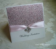 Luxury Glitter Wedding Invitation created using ivory pearlised card. The front has been layered with pink quartz glitter card and wrapped with a pink satin ribbon threaded through a diamante heart. Wedding Invitation wording on front of card has been embellished with small