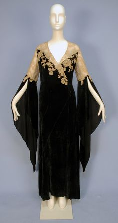 VELVET and LACE DESHABILLE, with WIZARD SLEEVES, 1930's. Black bias cut silk panne velvet wrap with off center self button and loop closure, having sheer ecru Alencon lace bodice top and applique to velvet, curved skirt gores, lace topped long, pointed sleeve open from above the elbow, inside tie at waist. B-42, L-60. (1/2 inch hole near hem, few very tiny holes in lace)