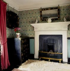 fireplace in Beatrix Potter's bedroom at Hill Top, Sawrey with a red curtain on the window.