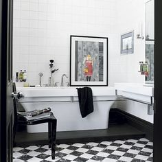A monochrome and silver theme in this bathroom creates a chic, modern effect, with the checked tile-effect floor adding a traditional edge. A casually placed piece of art adds a personal touch, while the in-built wall TV denotes luxury.