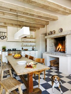 A wood-burning fireplace designed for cooking adds Mediterranean charm to this eat-in kitchen. It's easy to create an intimate mood for a dinner party with a communal farmhouse table and flickering flames. Design by Oz Architects; photography by Werner Segarra
