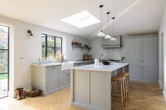 Three delicate pendant lights hang above a lovely big central island in our new Chester Kitchen project