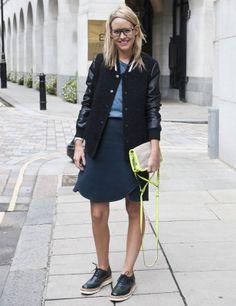 Look Oxford-Look universitario con chaqueta de tweed negra con mangas de cuero, falda-pareo azul oscura, top básico azul celeste, zapatos  masculinos y bolso gris con toques de color en amarillo flúor.