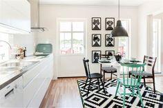 Monochrome kitchen.  Black pendant light.  Black and white prints.  THAT green chair.